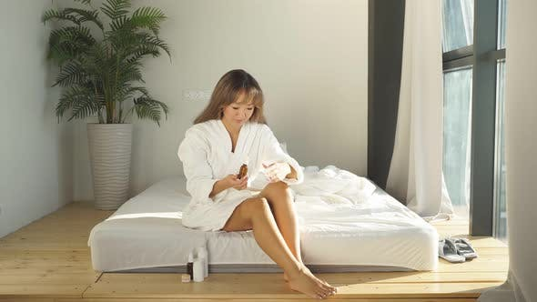 Portrait of a Young Woman in a Bathrobe Sitting on a Bed She Takes Care of the Skin of Her Feet
