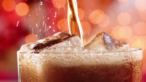 Glass of Cola. Ice Cola with Splashing Bubbles Slow Motion on a Blurry Light ,Blurry Background
