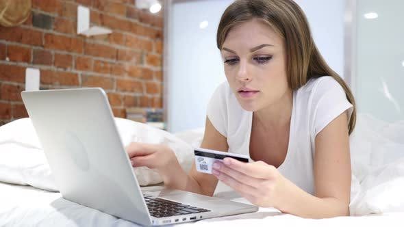 Cover Image for Online Shopping by Woman in Bed, Payment by Credit Card