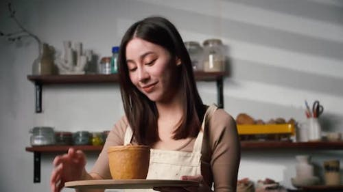 A female ceramicist is creating a new pottery in the workshop.