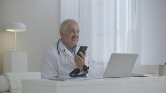 Experienced Therapist Is Consulting Patient or Chatting with Colleague By Cellphone, Sitting in