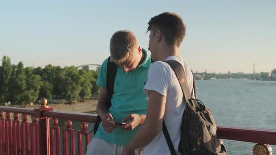 Thumbnail for Two Friends Teenage Boys Using Smartphone, Talking and Smiling