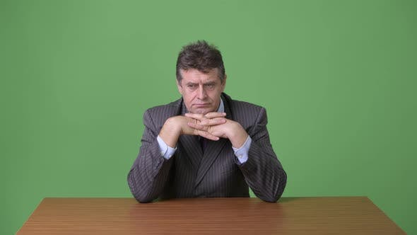 Cover Image for Mature Handsome Businessman Against Green Background