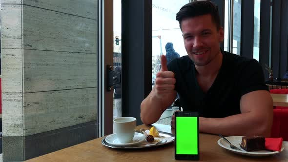 Thumbnail for A Man Sits at a Table in a Cafe and Gesticulates Excitedly Toward the Smartphone with a Green Screen