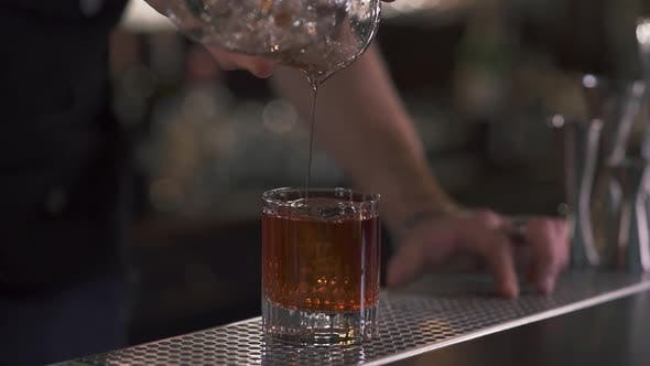 Thumbnail for Male Hand Bartender Pours Liquid in the Glass with Big Ice Cube in It