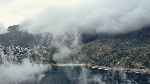 Thumbnail for Aerial Panning Shot of Mountain and Ocean Hiding Behind Thick Fog