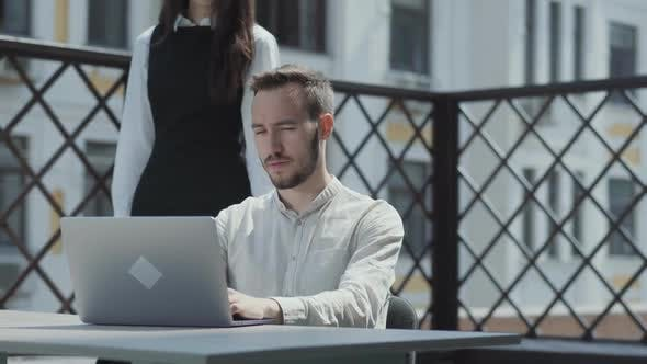 Thumbnail for Bearded Young Man Sitting at the Table on the Terrace in Front of Laptop, Working