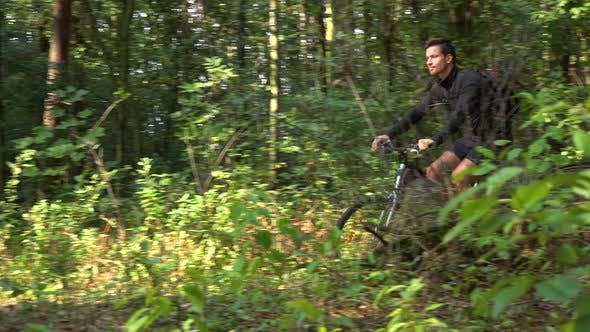 Thumbnail for A Cyclist Rides Down a Path Through a Forest - Side View