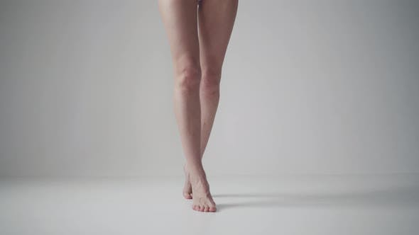 Cover Image for Slender Female Legs - Girl Goes To the Camera on Tiptoes on a Light Background