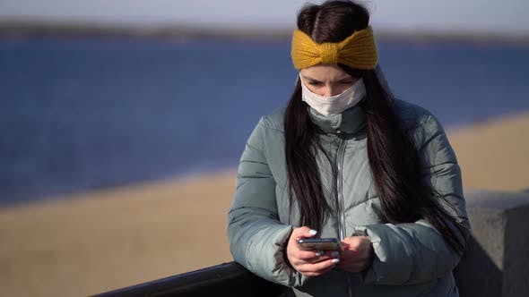 Thumbnail for Young Woman Wearing a Mask Texting on the Smartphone
