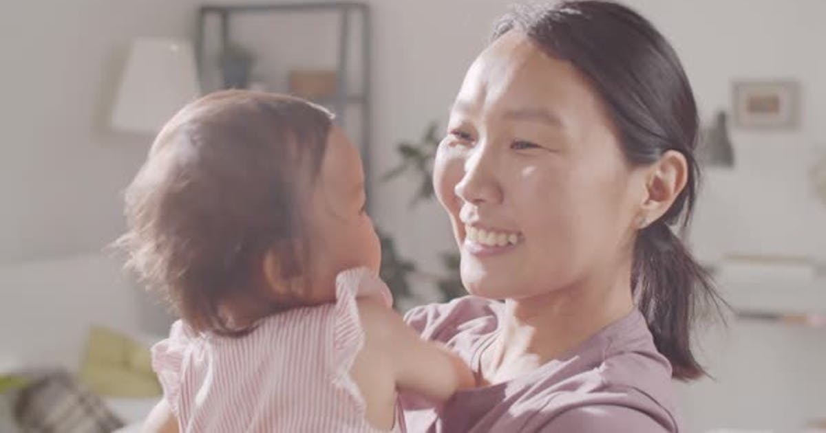 Portrait of Happy Asian Mother with baby Daughter on Arms