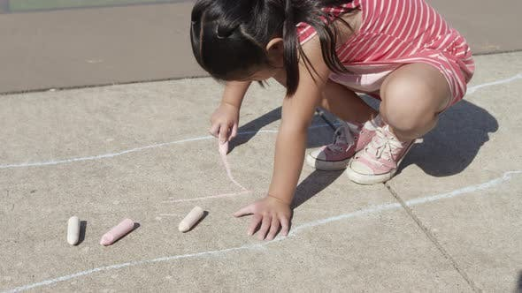 Thumbnail for Young girl playing Hopscotch at park, drawing with chalk