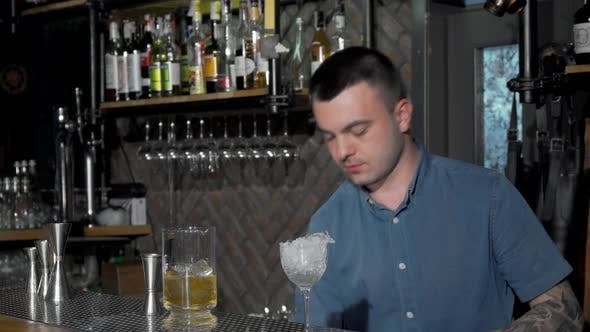 Thumbnail for Handsome Bartender Preparing Cocktail at the Bar