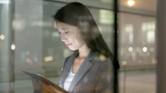Thumbnail for Business woman look at smart phone with window reflection at night