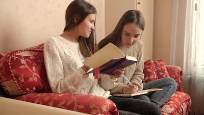 Two Happy Smiling Schoolgirls Smiling While Sitting on Sofa and Writing in Diaries