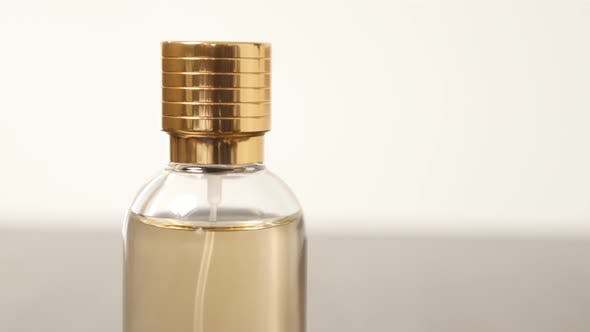 Thumbnail for Golden fragrance color in golden cap bottle slow tilt 4K 2160p 30fps UltraHD footage - Parfume bottl