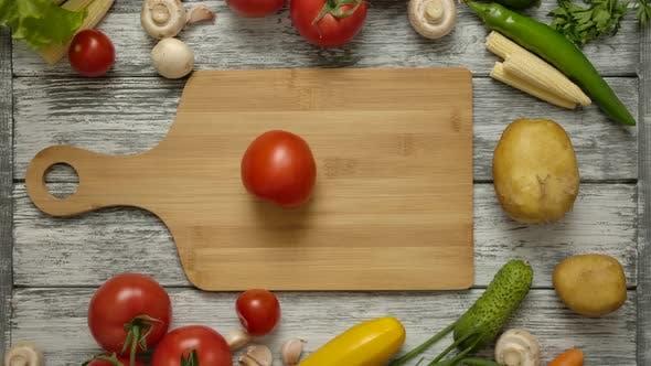 Thumbnail for Männliche Hand drehende rote Tomate auf einem Holzbrett.