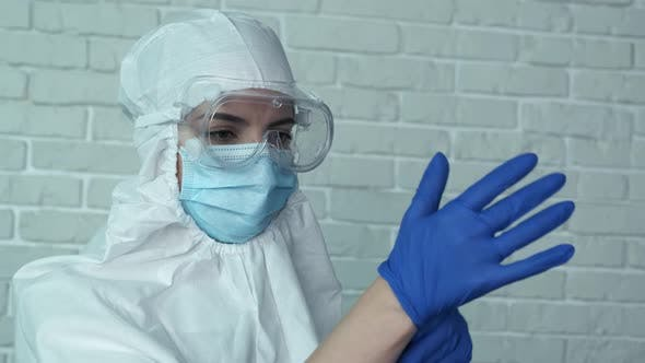 Woman Doctor Wearing Medical Latex Gloves To Fight Coronavirus Pandemic Covid-2019. Protective Suit