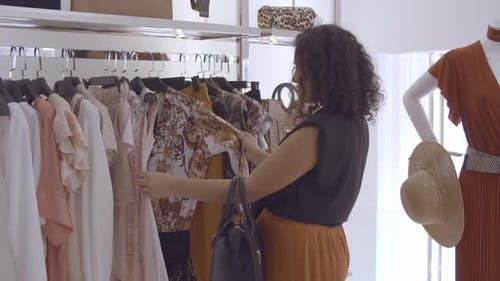 Black Haired Lady Choosing Clothes and Browsing Dresses