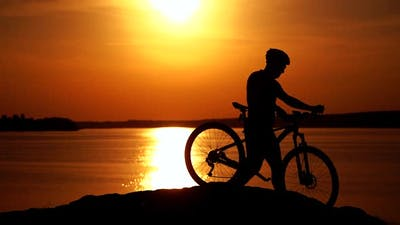 Biker riding on bicycle on hill. Cyclist with mountain bike on rocky trail at sunset