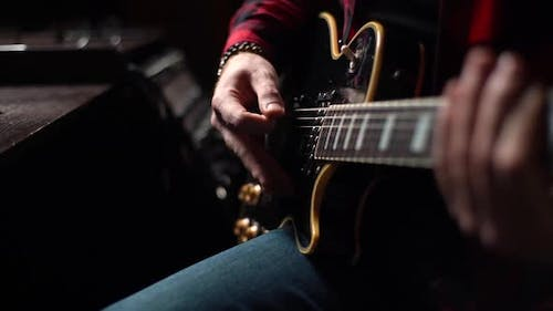 Closeup of Hands of Unrecognizable Musician Playing Solo Guitar Part on Electric Guitar at Studio