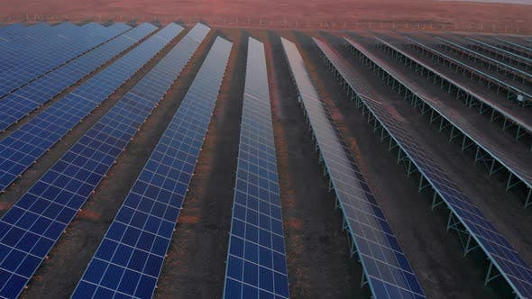 Aerial Drone View Into Large Solar Panels at a Solar Farm at Early Spring Sunset. Solar Cell Power