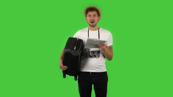 Thumbnail for Tourist with Suitcase in Hand and Retro Camera Carefully Examines Map,then Looking at Camera and