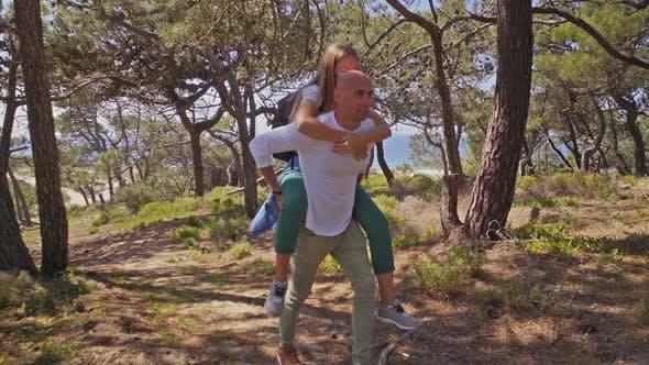 Man Piggybacking Girlfriend in Forest