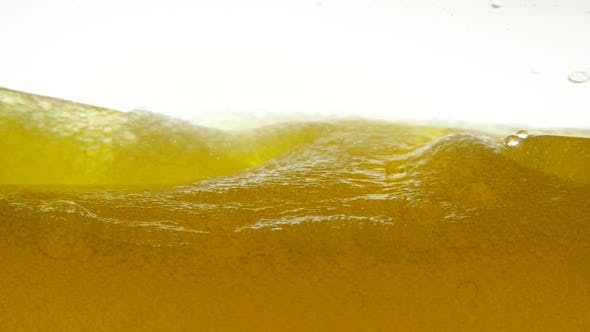 Thumbnail for Golden Liquid with Bubbles on a White Background, Which Was Sharply Stirred with a Teaspoon. Close