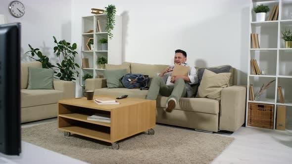 Man Bringing Takeaway Food, Sitting on Sofa and Turning on TV