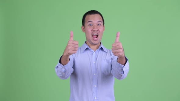 Thumbnail for Studio Shot of Happy Asian Businessman Giving Thumbs Up and Looking Excited