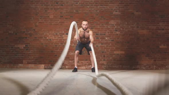 Thumbnail for Athletic Young Man with Battle Rope Doing Exercise in Functional Training Fitness Gym