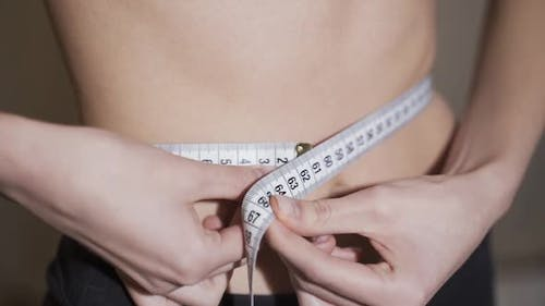Waist Measurement. A Woman Measures Her Waist with a Centimeter Tape.