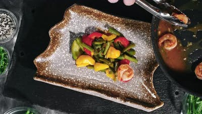 Cook Putting Shrimps and Vegetables on Plate