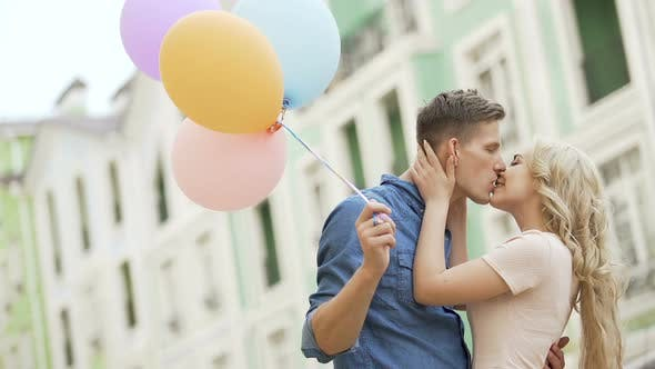 Cover Image for Couple walking down street, stopping to kiss, guy holding balloons, feelings