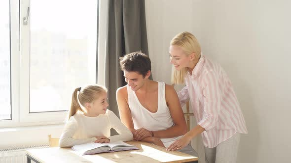 Father and Mother Help Their Daughter Do Their Homework