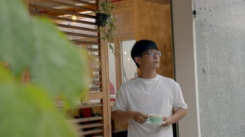 Asian Man with Glasses Teenager, Went Out To the Terrace Near the House, Enjoying the Weather and