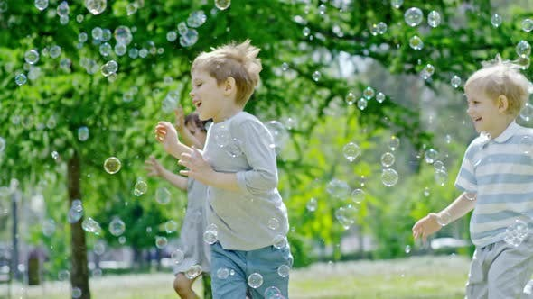 Thumbnail for Excited Children Running through Lots of Soap Bubbles in Park