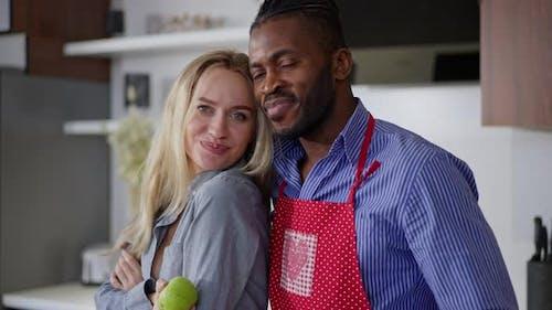 Medium Shot of Joyful Interracial Couple Posing in Kitchen at Home