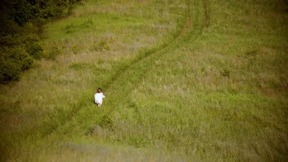 Thumbnail for A Little Girl in White Clothes Running on the Green Field