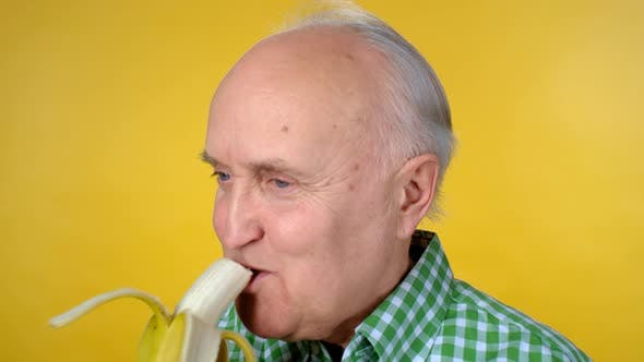 Cover Image for Portrait of Cheerful Senior Man Eating Banana