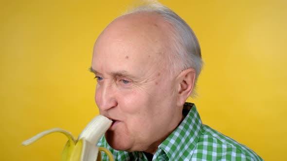Thumbnail for Portrait of Cheerful Senior Man Eating Banana