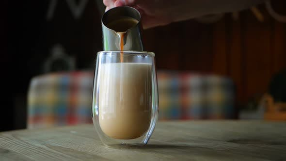 Barista Pours Milk Into a Coffee Glass for Latte