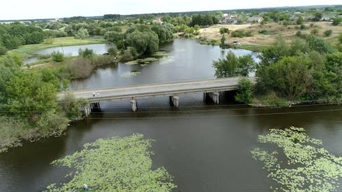 Aerial view of a picturesque river in the countryside with masonry and a concrete bridge