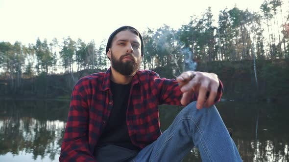 Thumbnail for Bearded Yung Man Sit Near Amazing Lake and Smoke Cigar