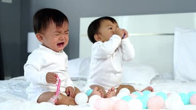 twin babies crying on a bed