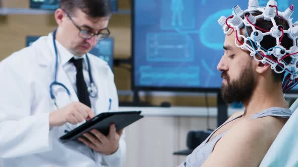 Patient Sitting on Hospital Bed and Wearing Brainwaves Scanning Headset