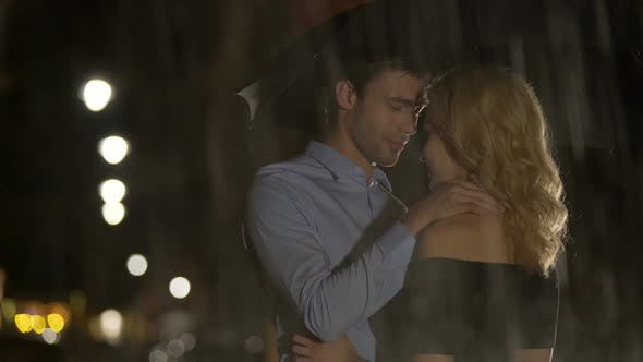 Cover Image for Man petting his blond girlfriend under the rain, couple waiting for taxi, love