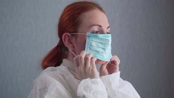 The Nurse Puts on a Protective Mask