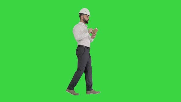 Confident Mature Man in Formalwear and Hardhat Writing Down Notes on a Green Screen, Chroma Key.